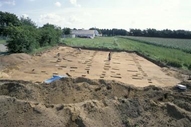 [:da]8000 år efter maglemosejægernes ligbål, blev der bygget et jernalderhus på stedet.[:de]8000 år efter maglemosejægernes ligbål, byggede man i jernalderen et hus hen over graven uden at vide, at den lå der.[:]