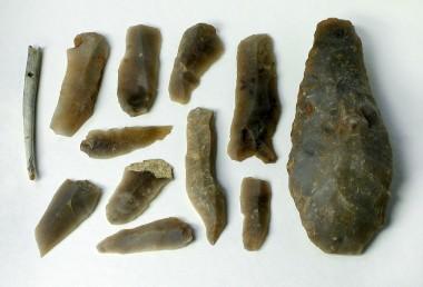 Den gravlagtes værktøjskasse i form af økse flækker og nål.