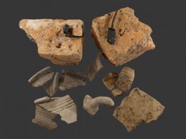 En kniv, en lysepibe og forskelligt keramik, hovedsageligt fra kander. Bemærk poteaftrykkene i murstenene.