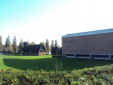 Den moderne museumsbygning står i kontrast til frilandsmuseets bindingsværkshuse.