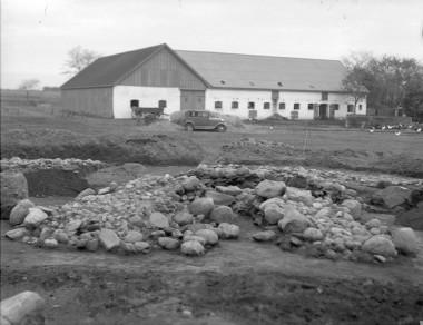 [:da]I højre side ses en lærredssæk, som dækker over den anden urne. Foto: Hans Neumann.[:de]4. Den centrale stenbunke, der var over den første urnegrav.[:]
