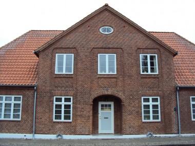 Facaden er inddelt af tre murblændinger, som indrammer vinduer og dør, hvilket giver et meget symmetrisk udseende.