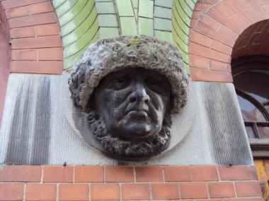 Vekselvirkningen mellem bygningens forskellige felter af grønglaserede sten, røde teglsten og pudsede dekorationer er typisk jugend.