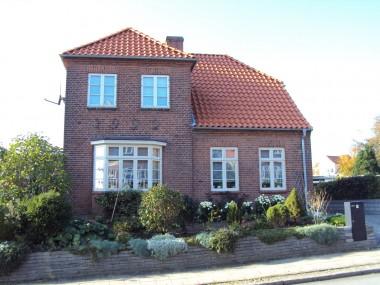 Vejen rummer forskellige huse, men alle har visse fællestræk; de røde mursten, de hvide vinduer og det røde tegltag.