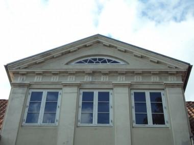 Gavltrekanten med friser og dekorationer inspireret af antikkens arkitektur. Pilastrene skal se ud, som de bærer gavltrekanten.