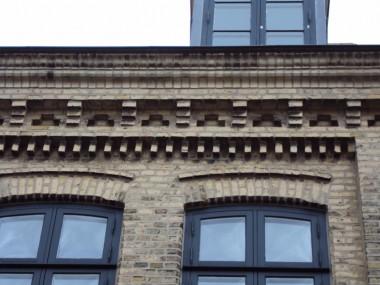 Detaljebillede af vinduesbryn og dekoreret frise under tagudhænget.